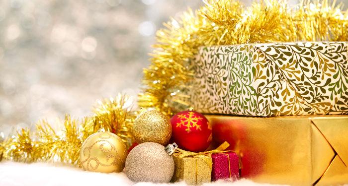 Geriausios kalėdinės dovanos, įpakuotos šventiškose auksinės spalvos ir raudonose pakuotėse, su kalėdiniais žaisliukais ir kalėdiniu geltonu blizgučiu