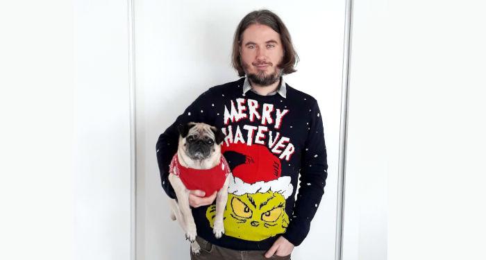 Vaikinas ir šuo su kalėdiniais megztiniais